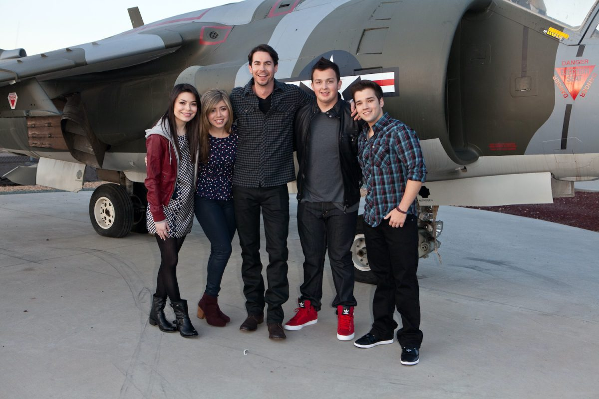 'iCarly' cast Miranda Cosgrove, Jennette McCurdy, Jerry Trainor, Noah Munck, and Nathan Kress pose in front of a plane in 2012