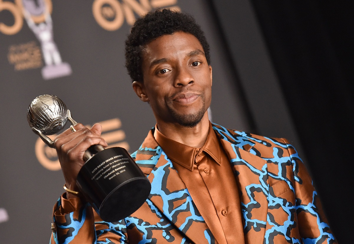 Chadwick Boseman holds his NAACP image award in a colorful suit.