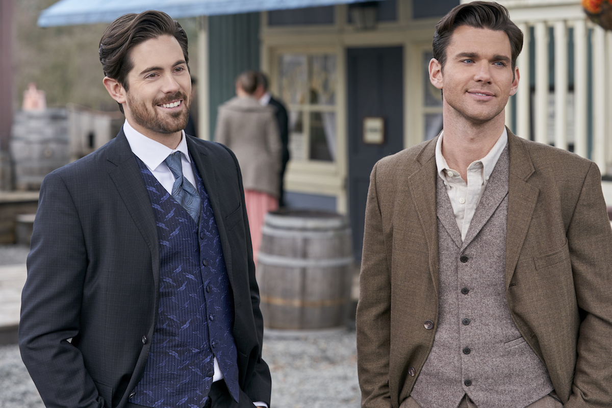 Chris McNally as Lucas, wearing a blue suit, and Kevin McGarry as Nathan, wearing brown jacket, standing next to each other on the street.