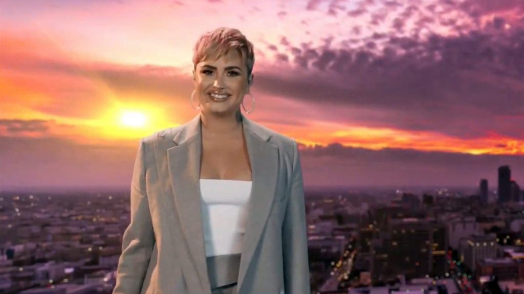 Demi Lovato smiling and standing in front of a sunset with her pink hair