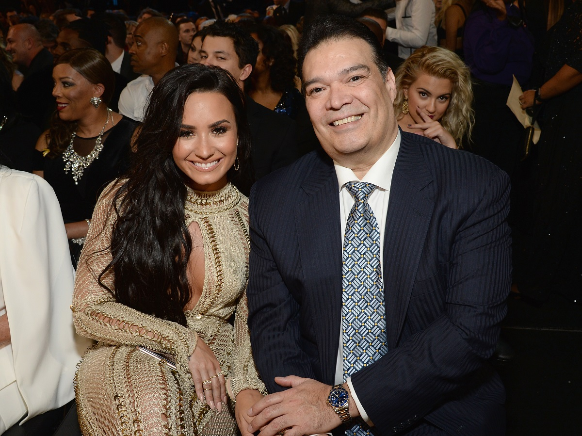 Demi Lovato holds hands with her dad, Eddie De La Garza, in front of a crowd