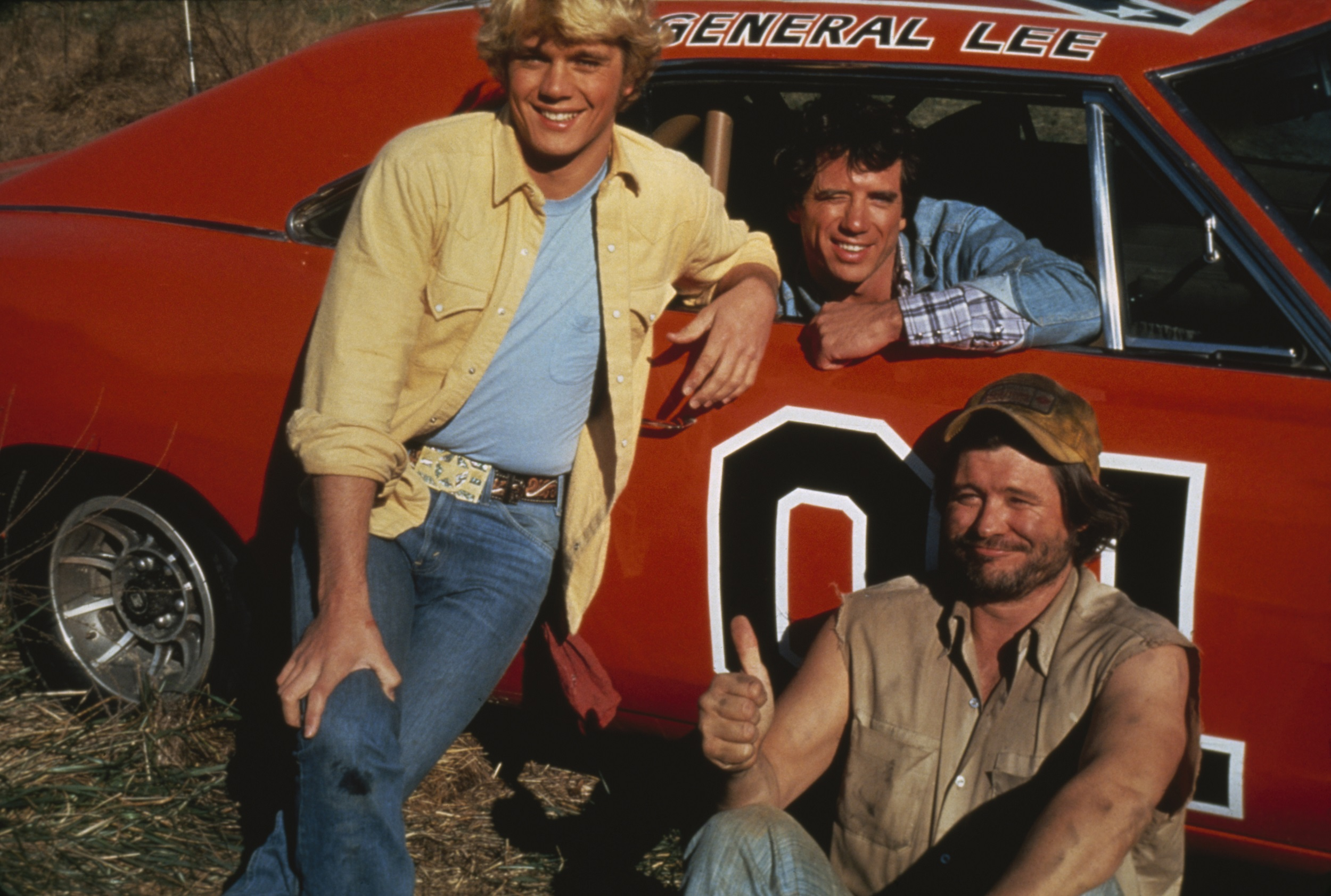 John Schneider, Tom Wopat, and Ben Jones as Bo Duke, Luke Duke, and Cooter. They are posing with the General Lee in The Dukes of Hazzard