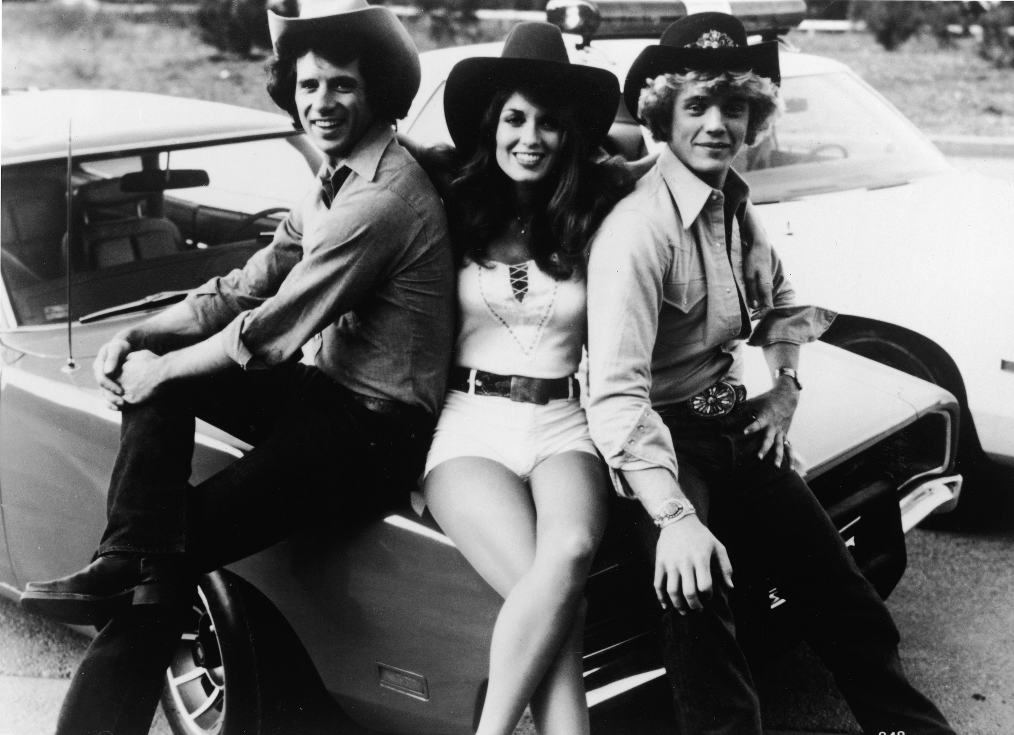 Tom Wopat, Catherine Bach, and John Schneider pose on The Dukes of Hazzard car, the General Lee