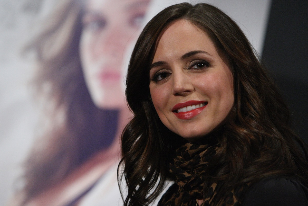 Eliza Dushku smiling in front of a 'Dollhouse' poster