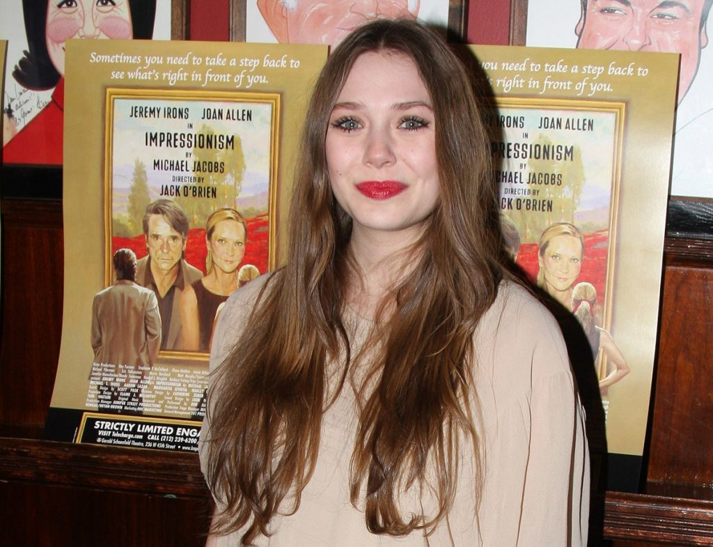 Elizabeth Olsen standing in front of a poster for her play 'Impressionism'