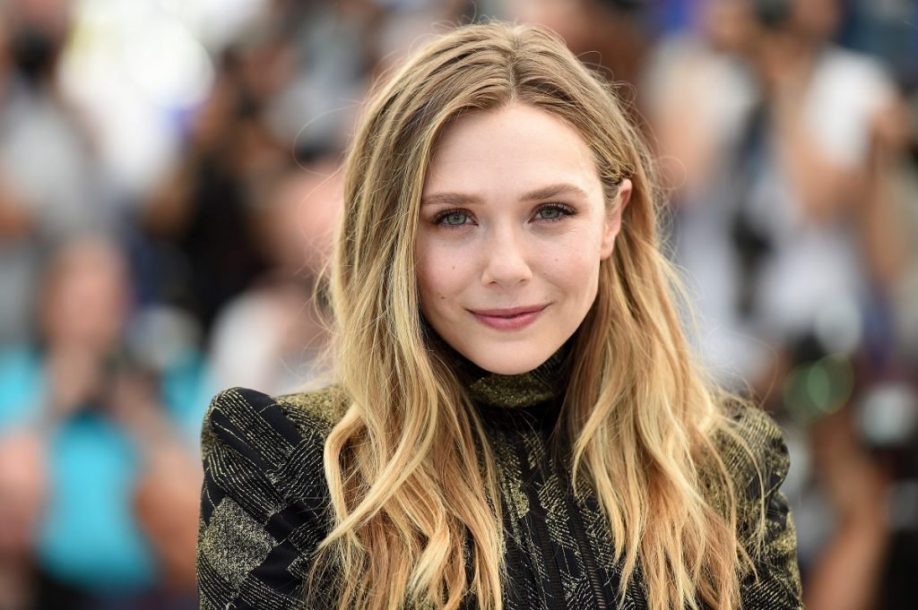 Elizabeth Olsen smiling in front of a crowd of people