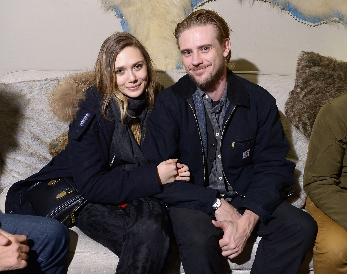 Elizabeth Olsen (L) holds Boyd Holbrook's arm while they sit on a couch.
