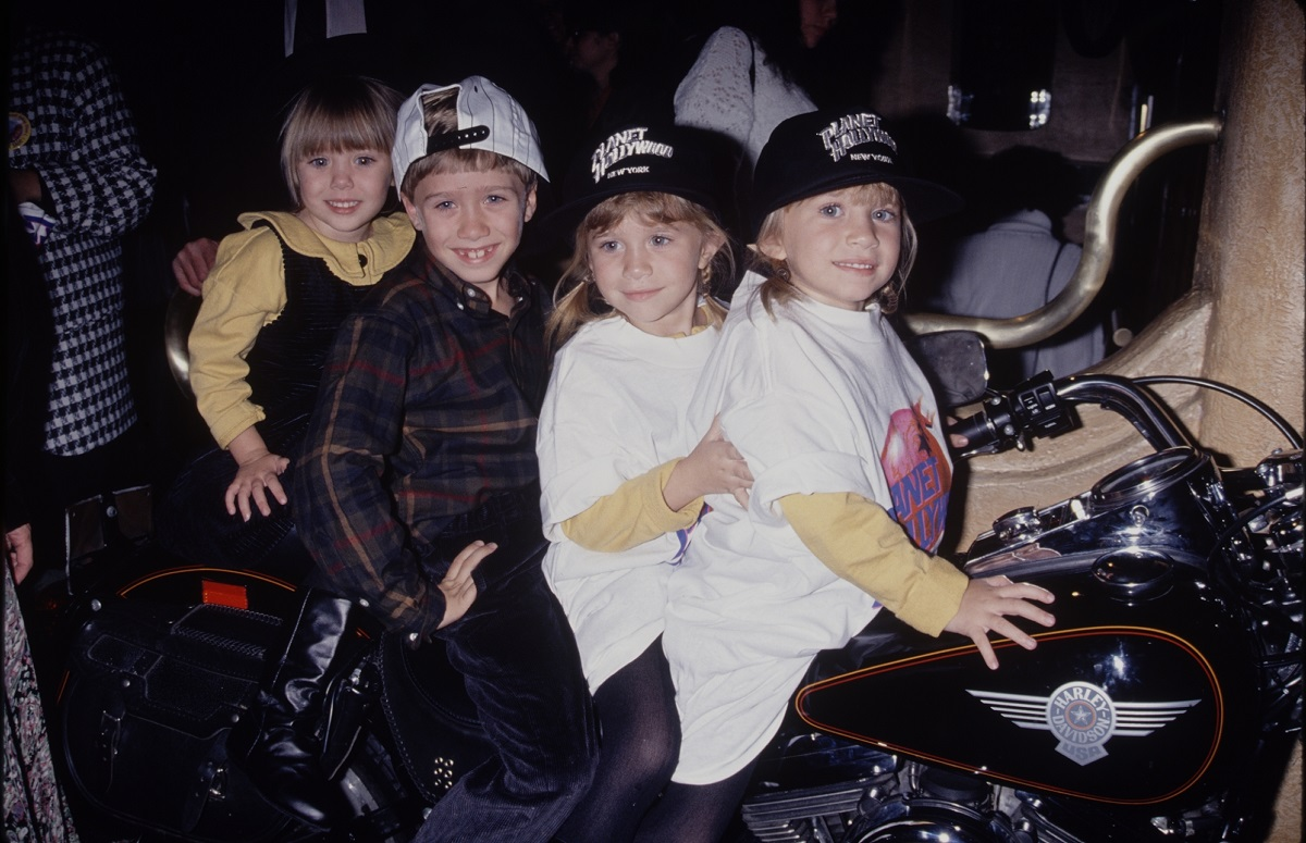 Elizabeth Olsen with siblings Trent, Mary-Kate, and Ashley sitting on a motorcycle