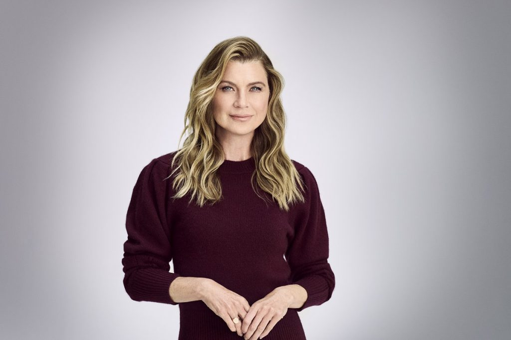 Ellen Pompeo in a maroon dress looking at the camera
