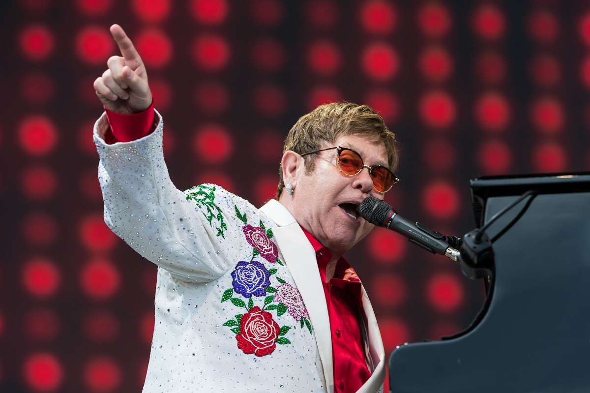 Elton John playing the piano and pointing