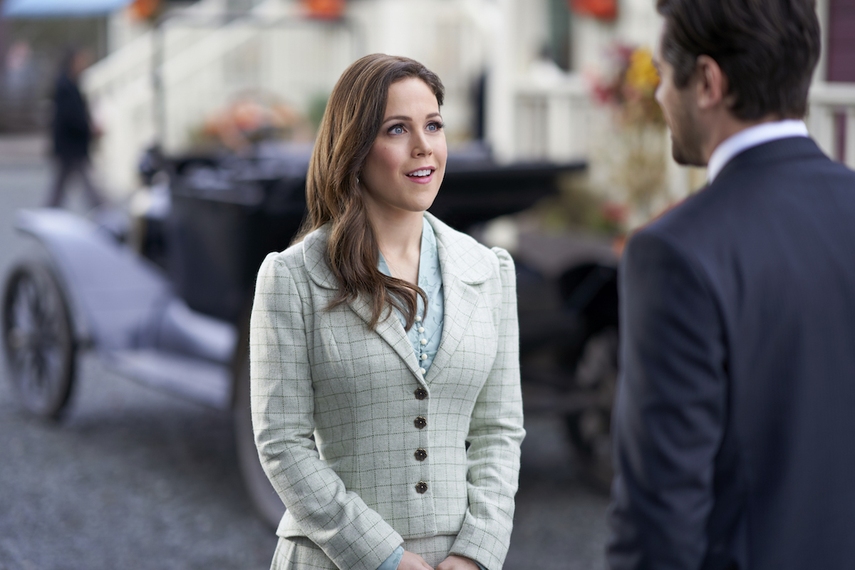 A smiling Elizabeth looks at Lucas, whose back is to the camera, in When Calls the Heart