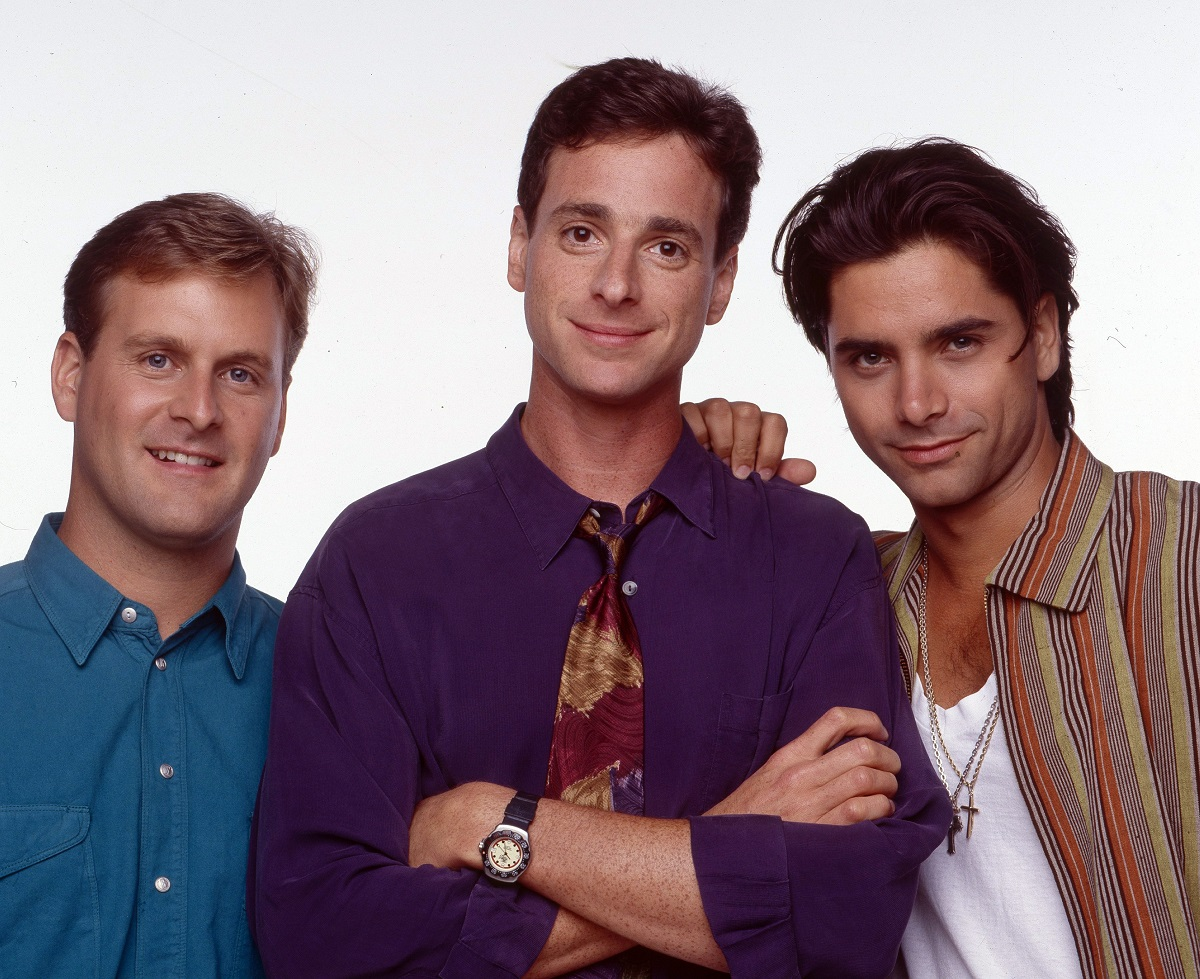 Dave Coulier, Bob Saget, and John Stamos on Full House pose against a white background