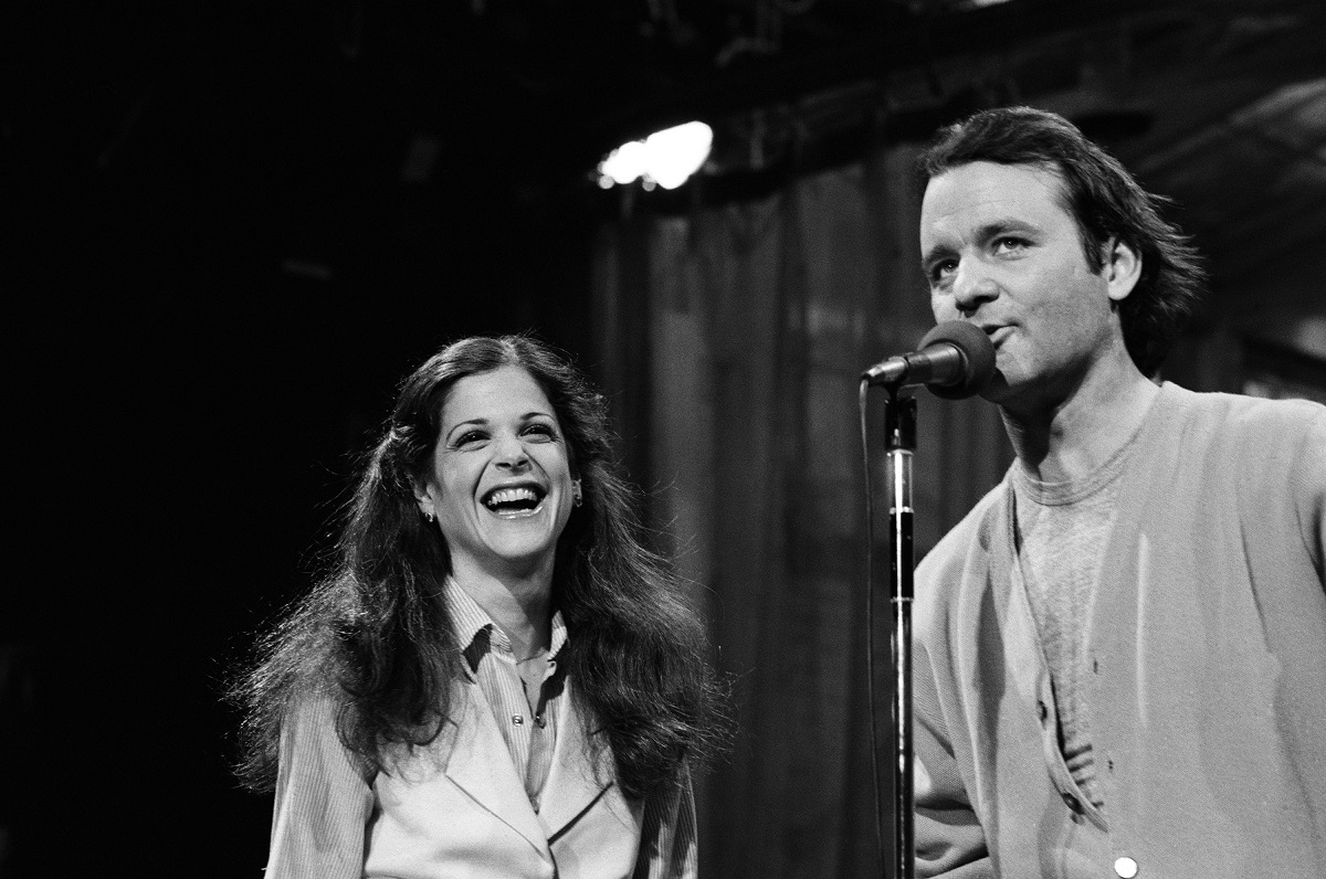 A black-and-white photo of Gilda Radner laughing at Bill Murray on the mic on 'Saturday Night Live'