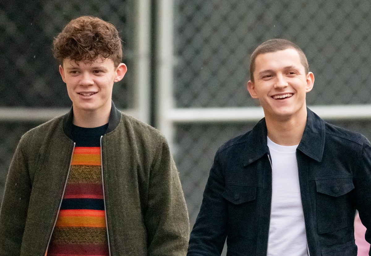 Tom Holland (R) and brother Harry Holland in front of a chain-link fence