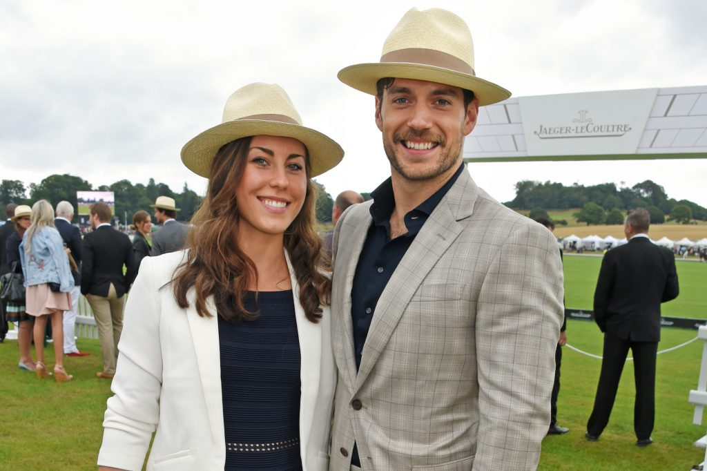 Henry Cavill's girlfriend, Lucy Cork, standing beside boyfriend Henry Cavill smiling at the camera outdoors