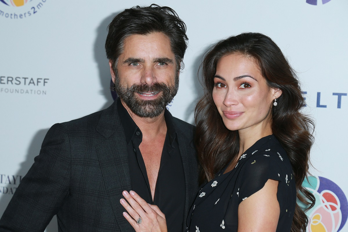 John Stamos' wife Caitlin McHugh with her hand on his chest