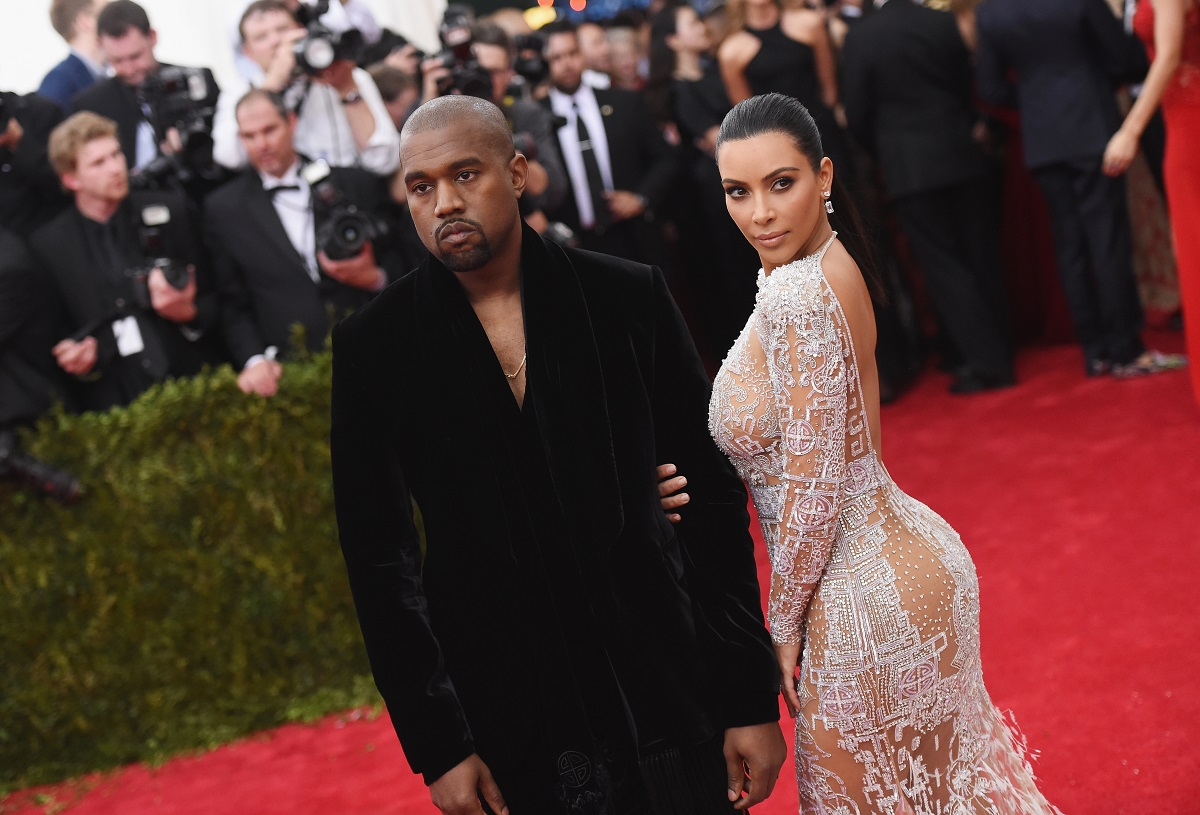 Kanye West (L) and Kim Kardashian posing on the red carpet in front of photographers