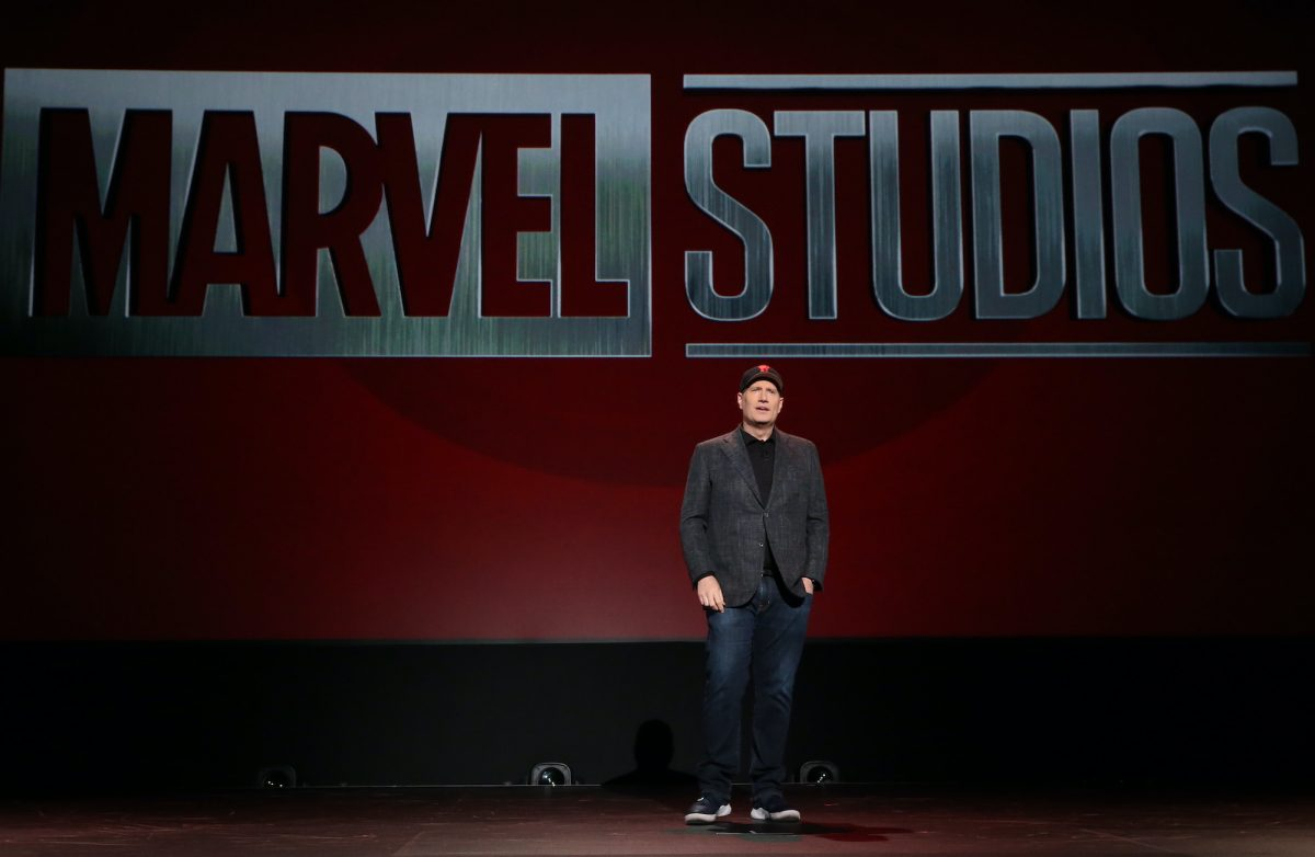 Marvel Studios president Kevin Feige stands on stage presenting new announcements to an audience