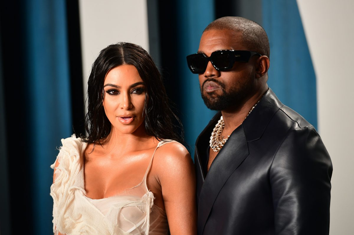 Kim Kardashian and Kanye West stand together on the red carpet at an award show.
