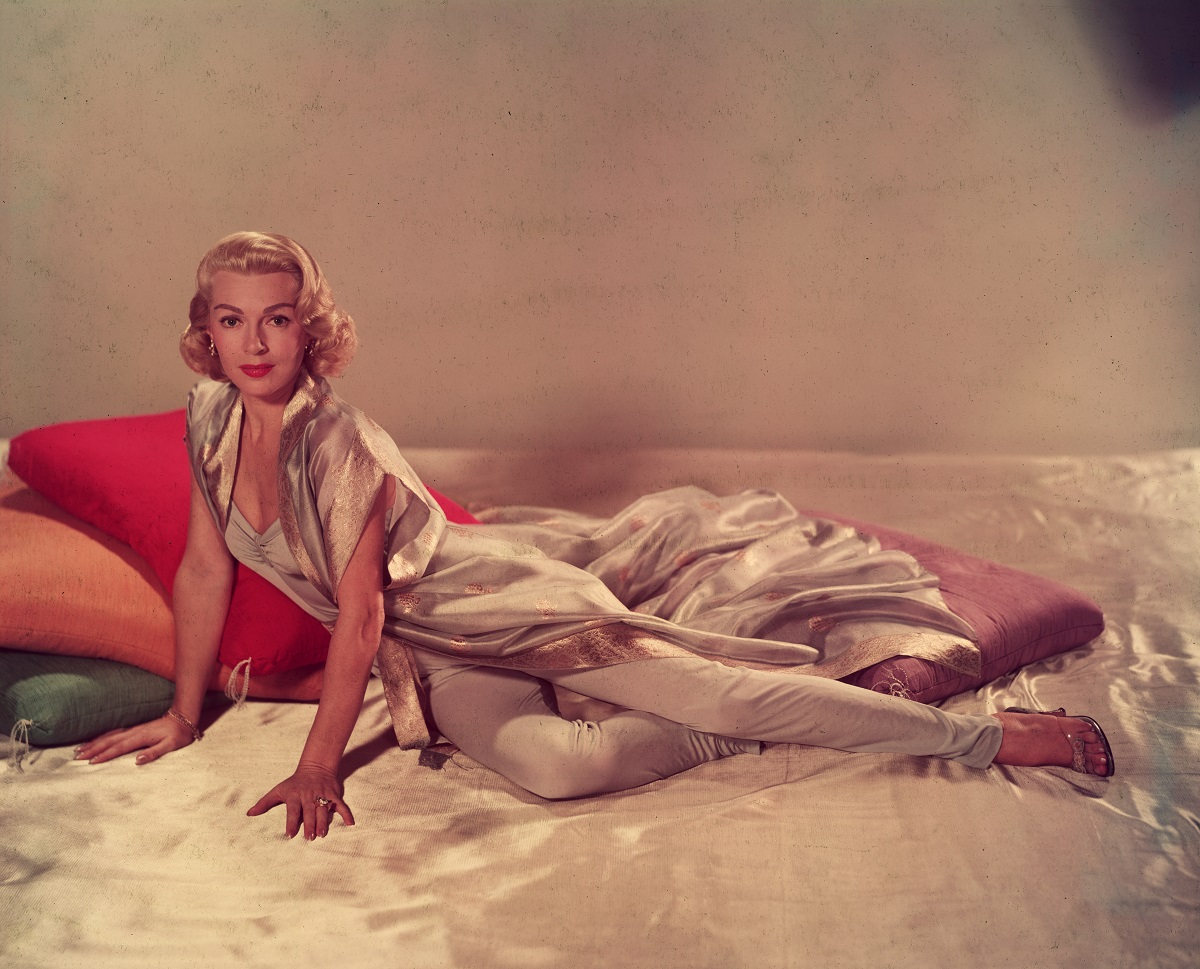 Lana Turner in 1955 posing on a silk sheet with large cushions in a sleeveless v-neck jumpsuit and a short-sleeved silk robe.