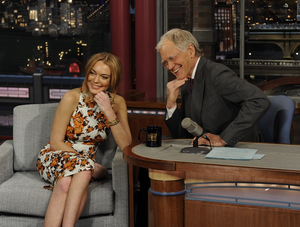Lindsay Lohan (L) and David Letterman sitting in chairs and posing with their hands on their chins.