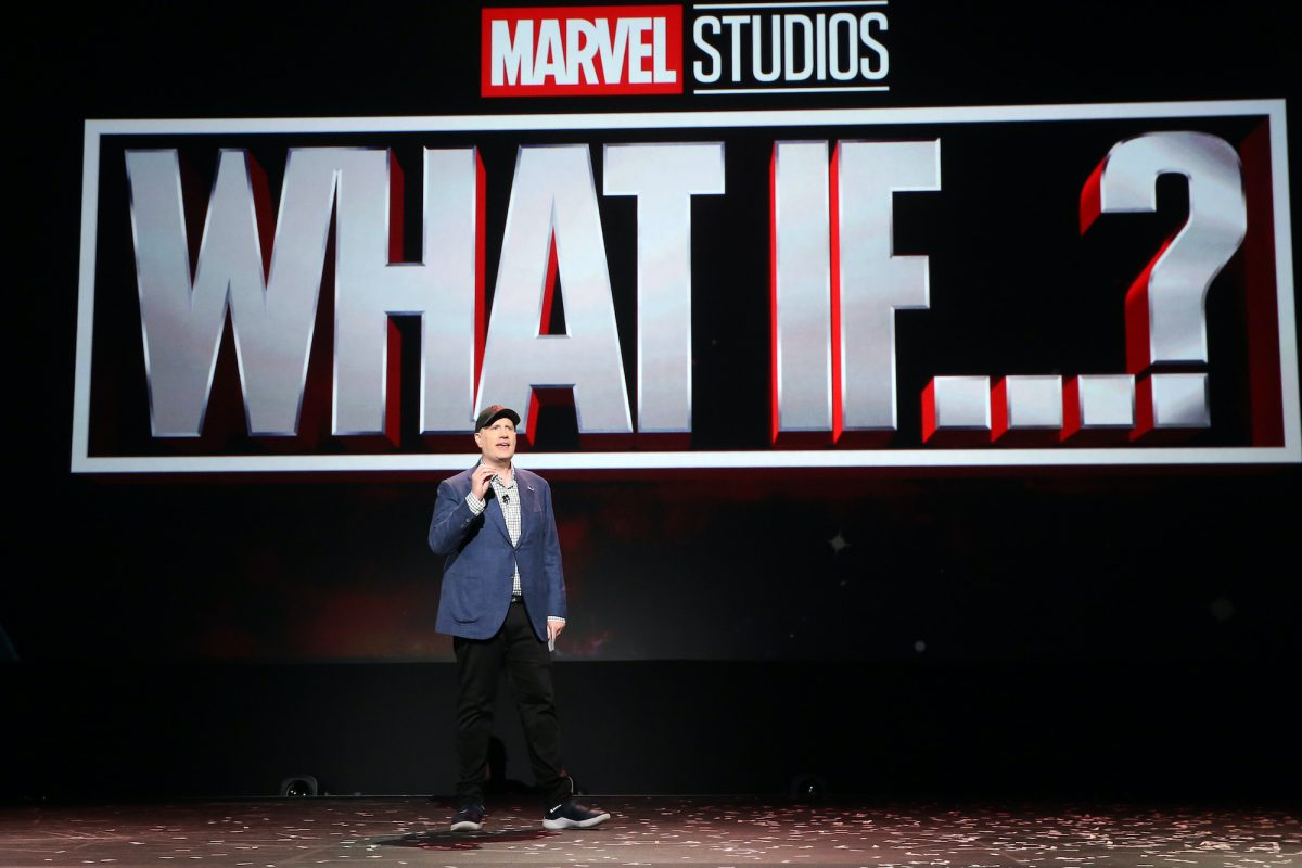 Kevin Feige stands onstage and speaks to an audience