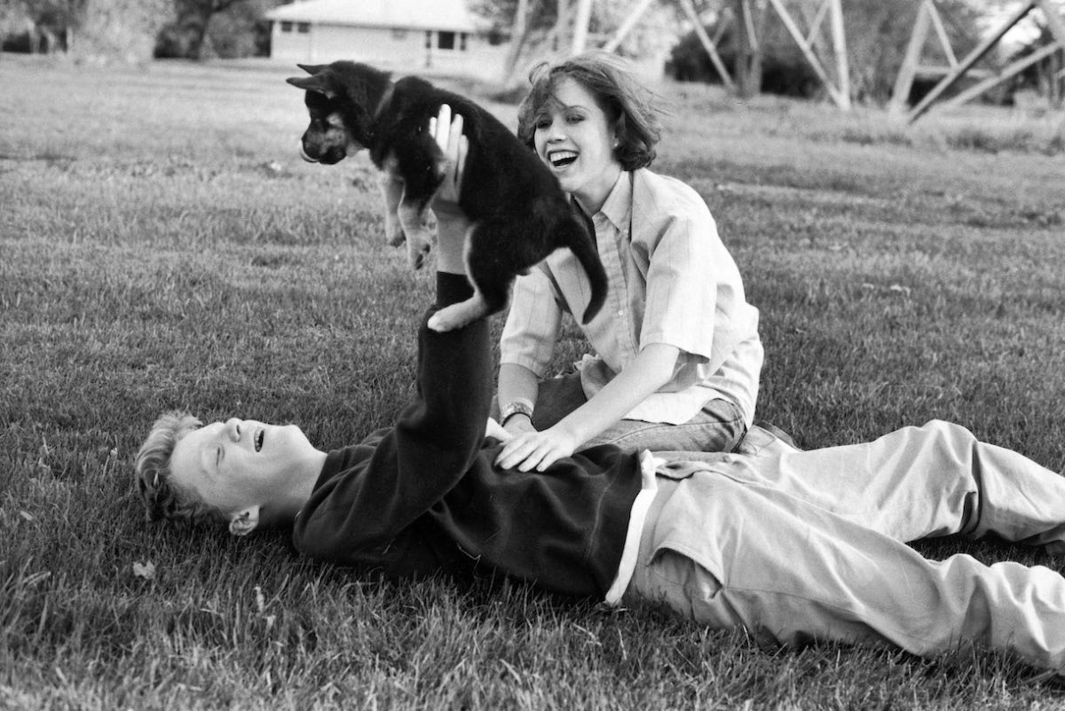 Actors Anthony Michael Hall and Molly Ringwald playing w. puppy during break in location shooting of 'The Breakfast Club'