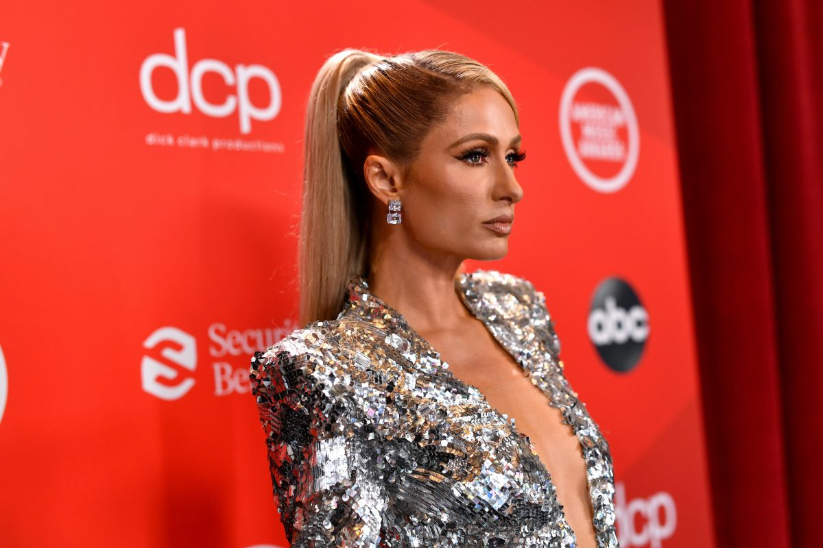 Paris Hilton stands on the red carpet at an awards show wearing a dress.