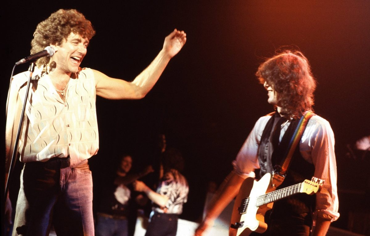 Robert Plant smiling and gesturing toward Jimmy Page on stage in 1983