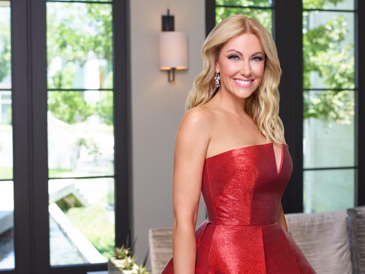 Stephanie Hollman smiling and wearing a red dress