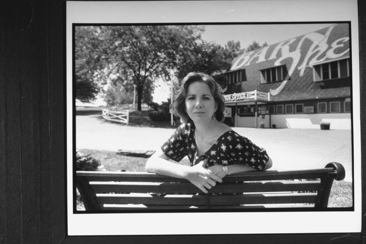 Melissa Gilbert posing on bench in front of the Barn Theatre where she was performing in her playwright husband Bo Brinkman's new play