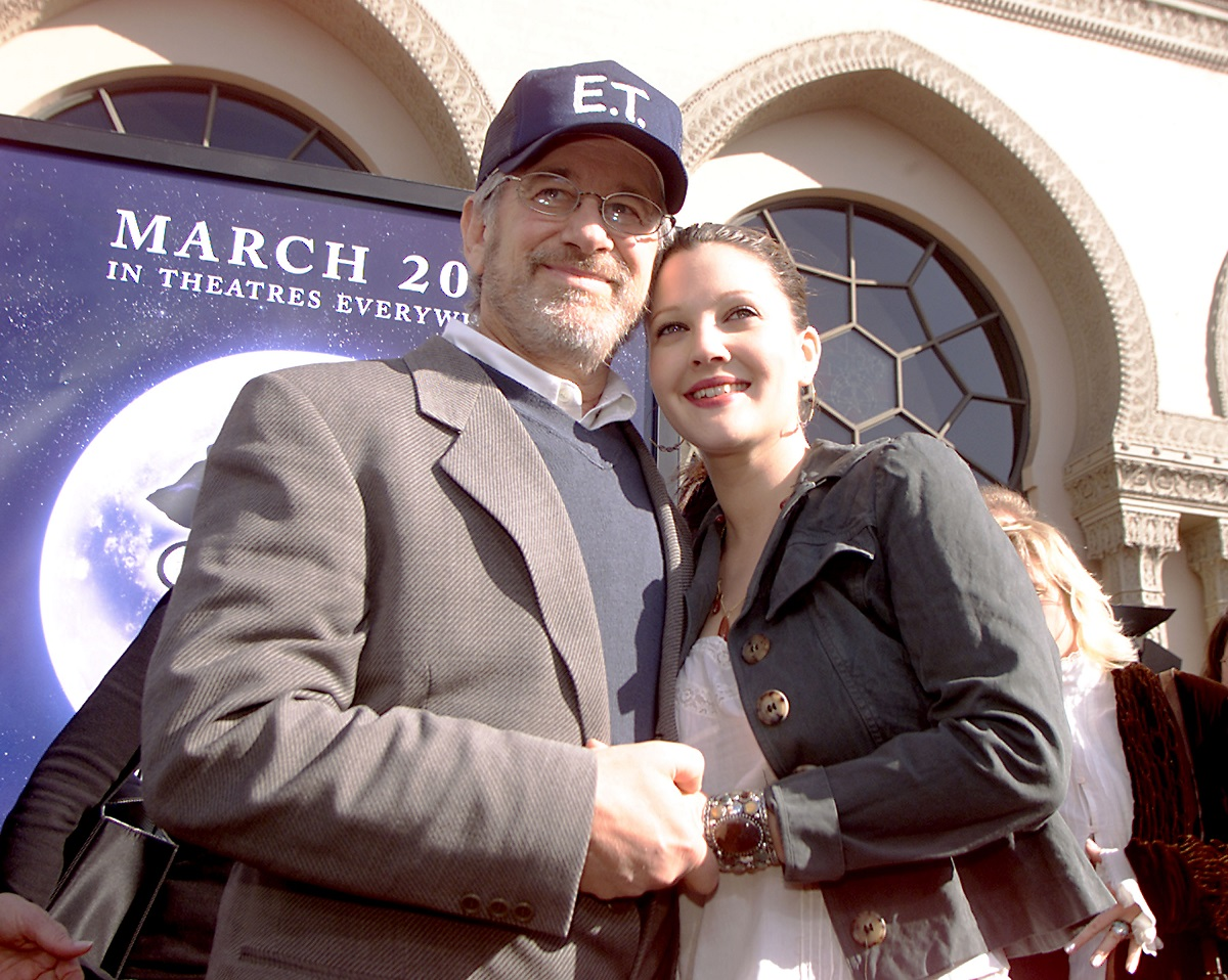 Steven Spielberg wearing an 'E.T.' baseball cap hold Drew Barrymore's hand