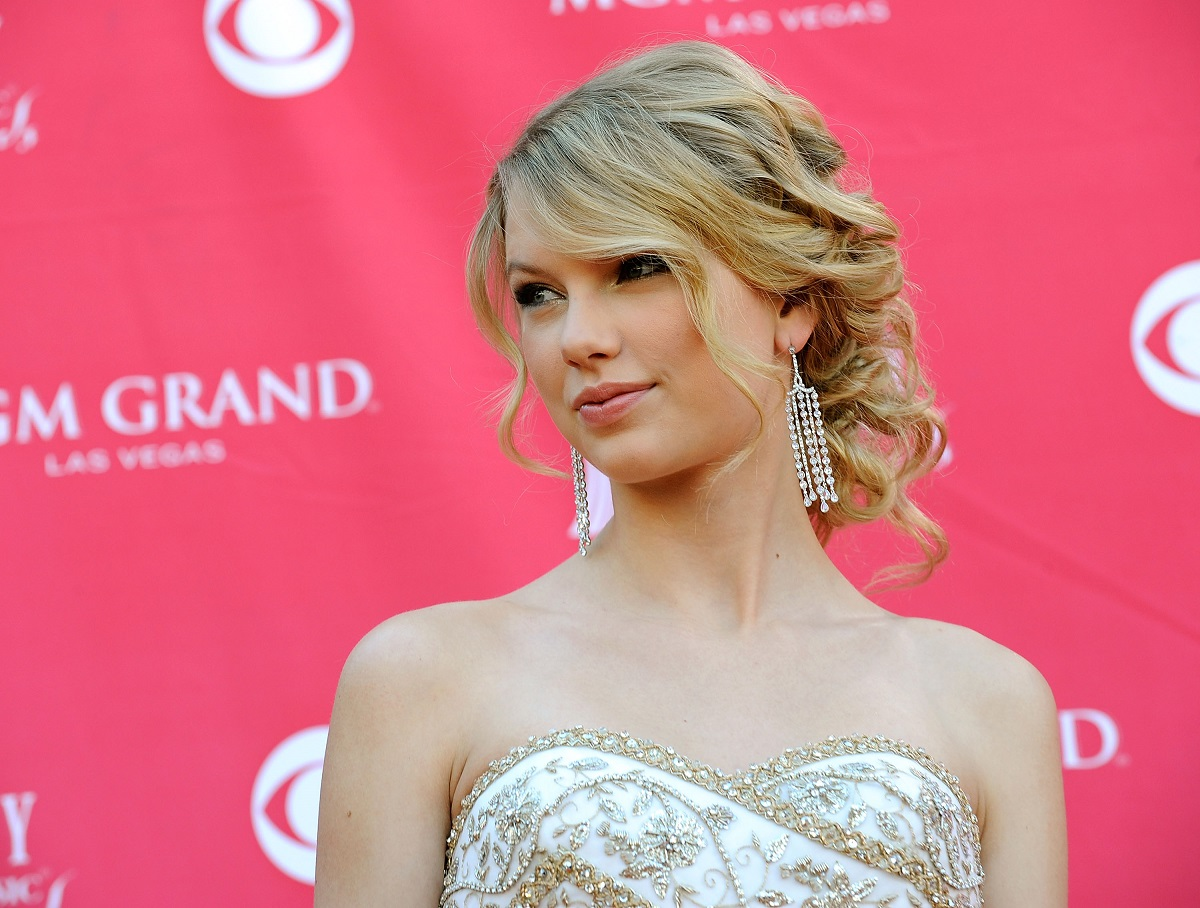 Taylor Swift looking to her right against a pink backdrop