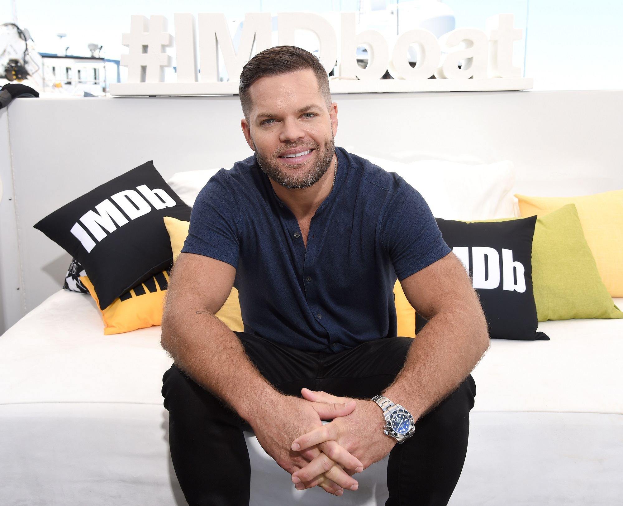 The Expanse star Wes Chatham sits on a white coach with IMDb throw pillows