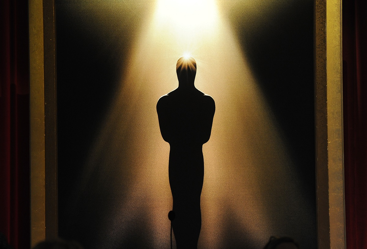 A spotlight reflects off the silhouetted Oscar statue.