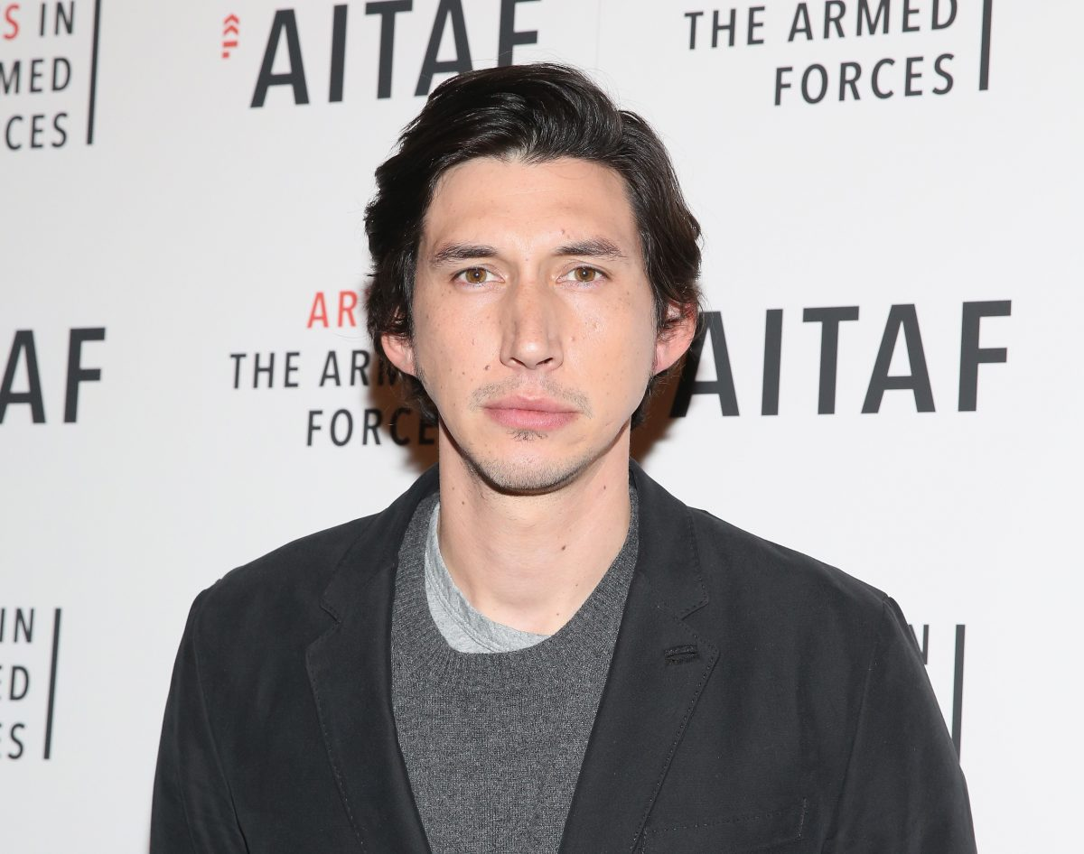 Adam Driver at a photo opportunity. He's looking at the camera, not smiling, wearing a grey sweater and black blazer.