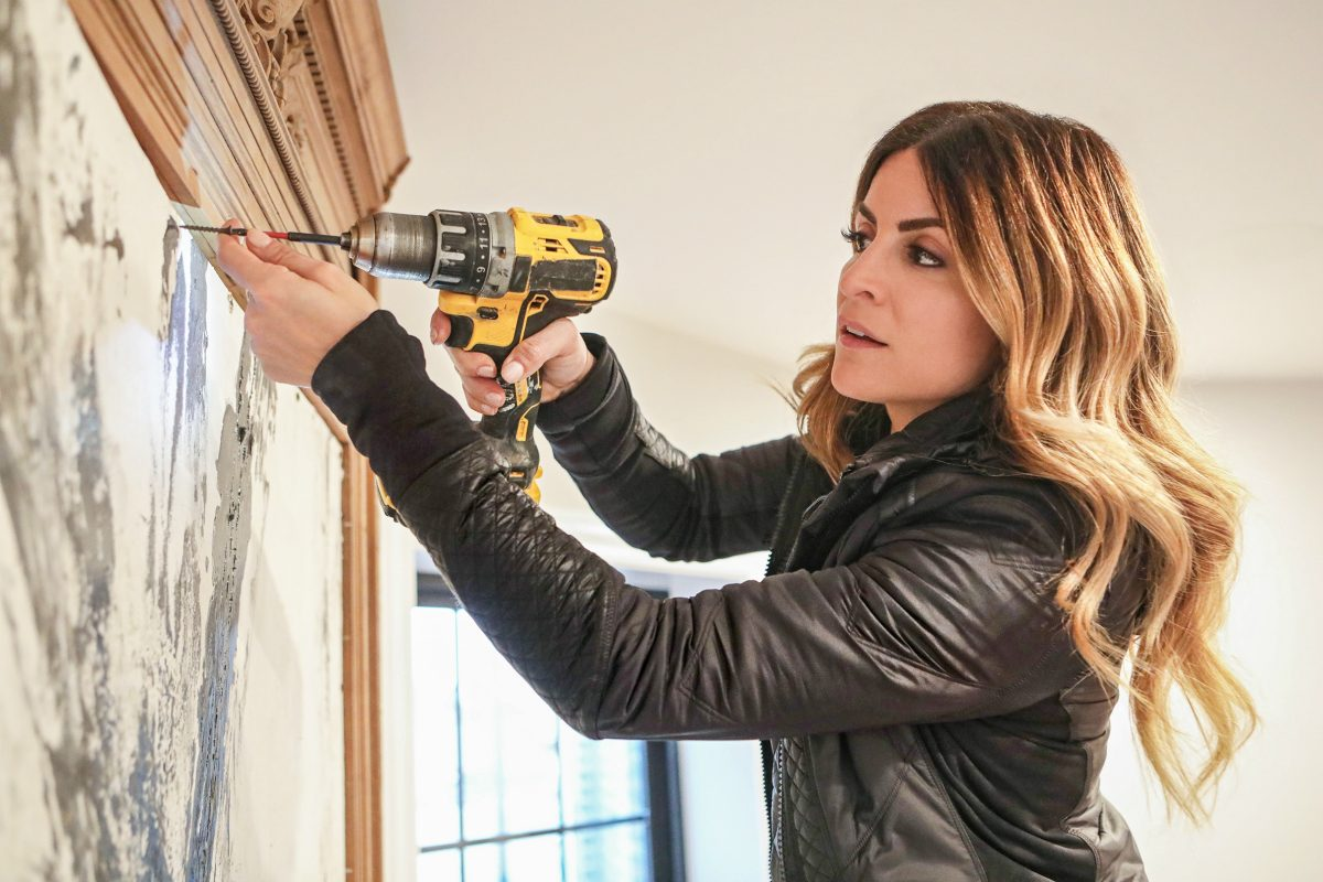 Alison Victoria holding a drill in episode of Windy City Rehab