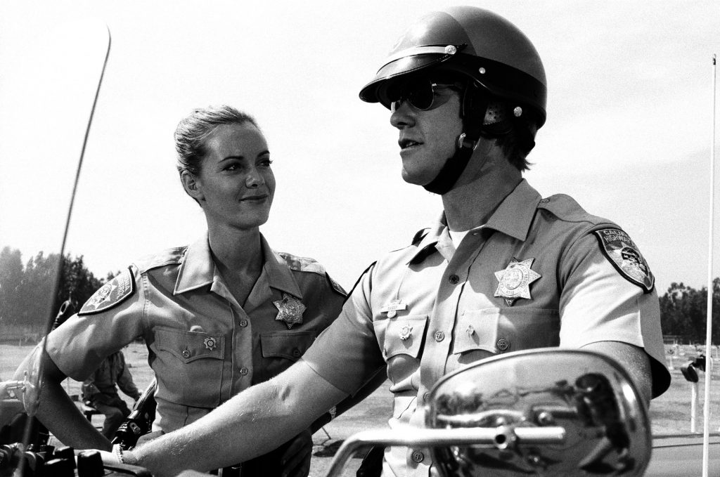 """A black-and-white photo of actors Anne Lockhart as Officer Kathy Mulligan and Larry Wilcox as Officer Jon Baker in 'CHiPs,' Episode 7, """"Return of the Supercycle,"""" aired on October 27, 1979"""