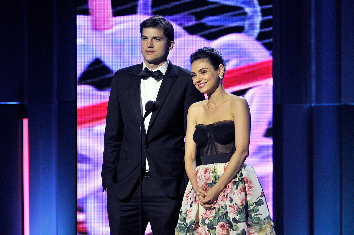 Ashton Kutcher and Mila Kunis stand next to each other onstage in front of a mic at the 2018 Breakthrough Prize