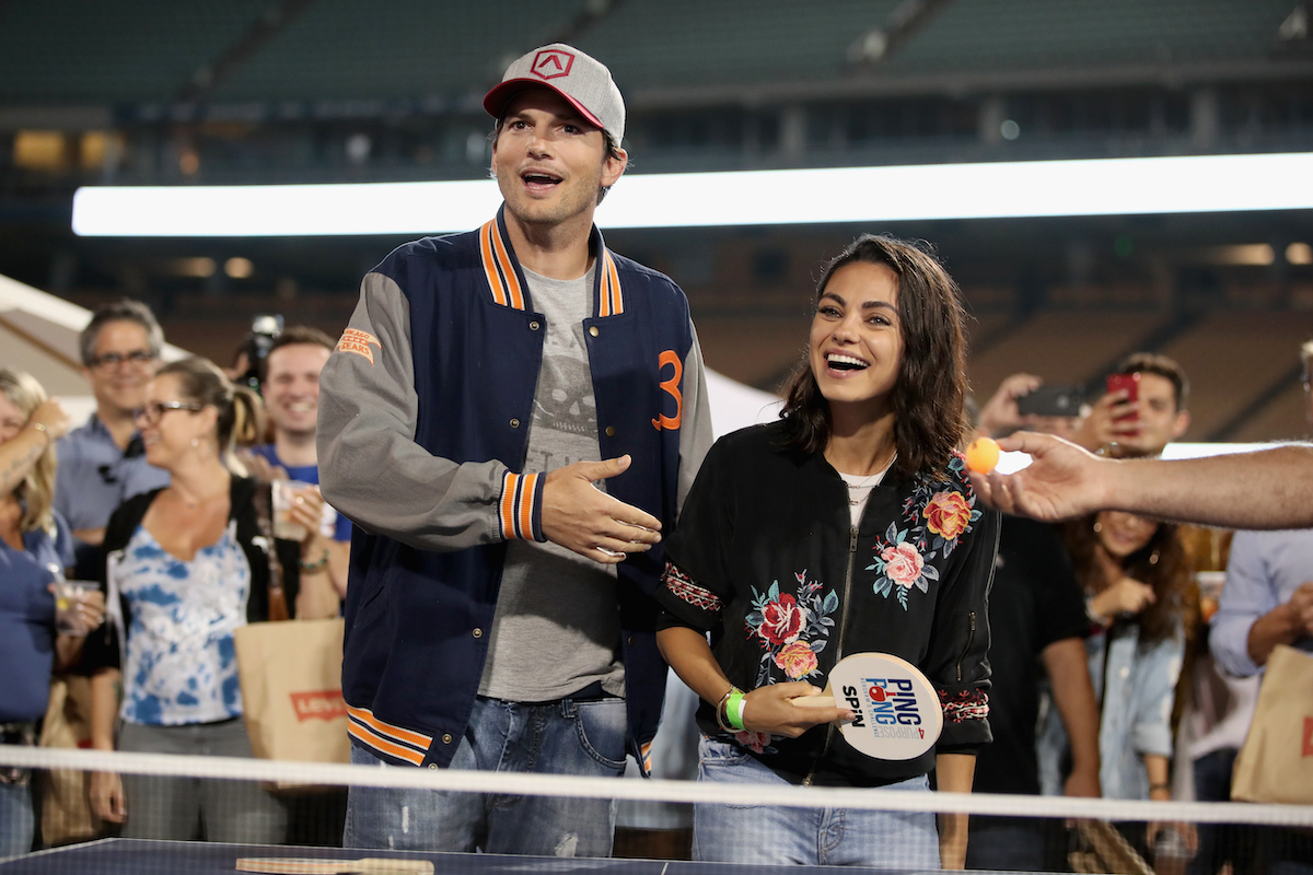 Ashton Kutcher and Mila Kunis stand next to each other at a ping pong table
