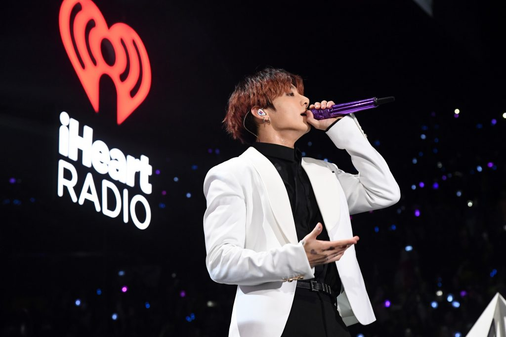 Jungkook of BTS sings into a purple microphone while performing during 102.7 KIIS FM's Jingle Ball 2019