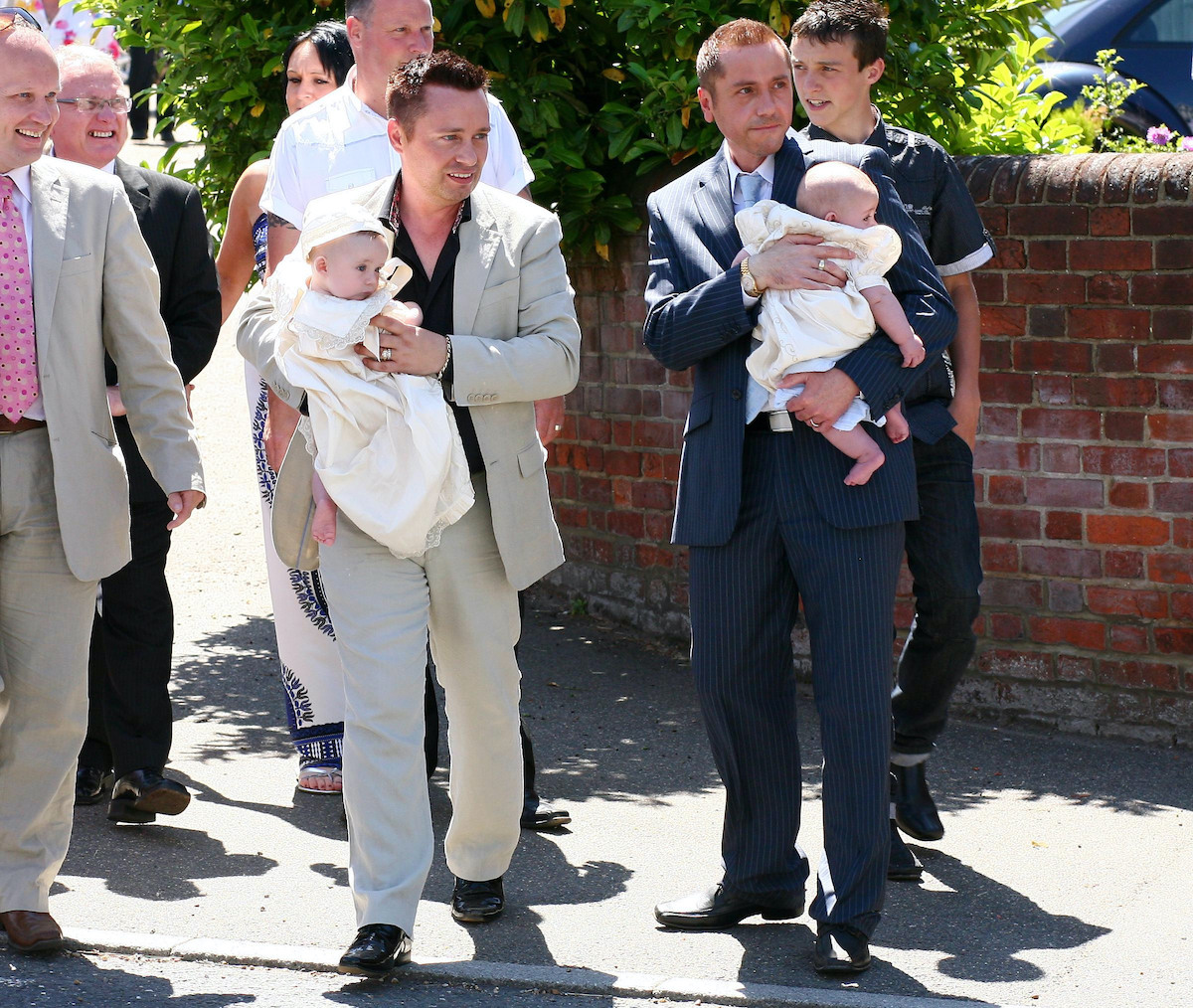 Gay couple Barrie and Tony Drewitt-Barlow carry their new twins Jasper and Dallas away from St. John the Baptist Church in Danbury, Essex