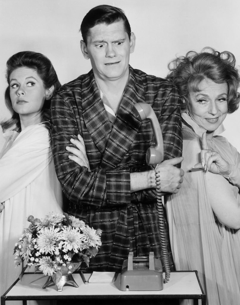 Elizabeth Montgomery, Dick York, and Agnes Moorehead, all wearing sleepwear, looking at a telephone with a levitating receiver, in a still from the television show, 'Bewitched'
