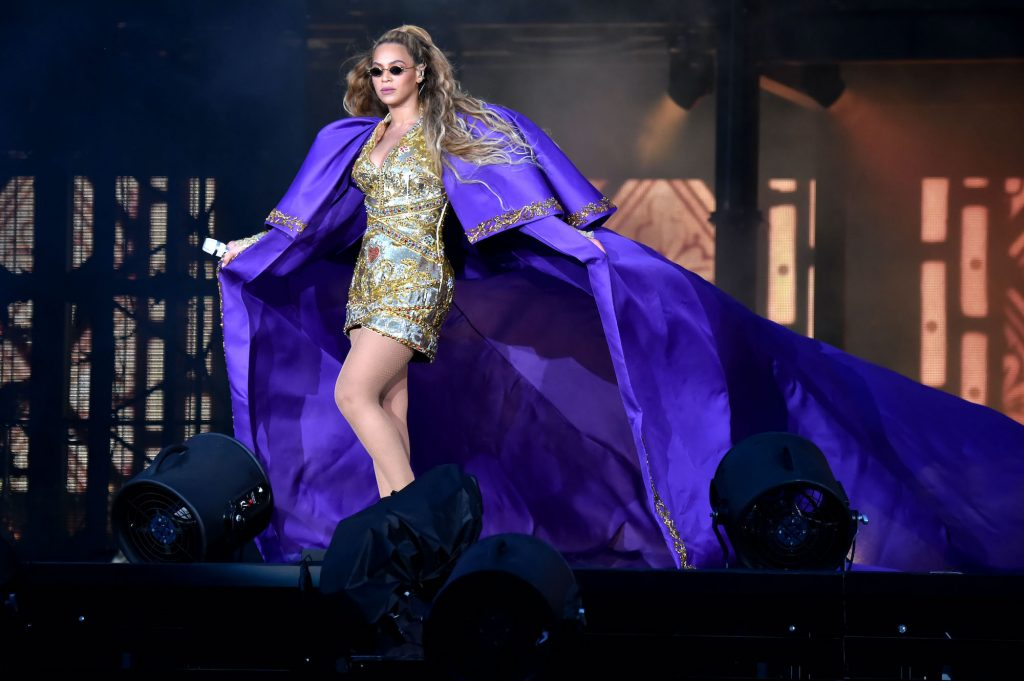 Beyonce walking on a stage wearing a large purple cape