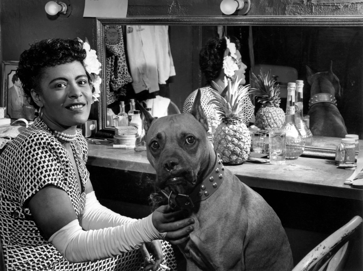A black and white photo of Billie Holiday smiling backstage with her dog.