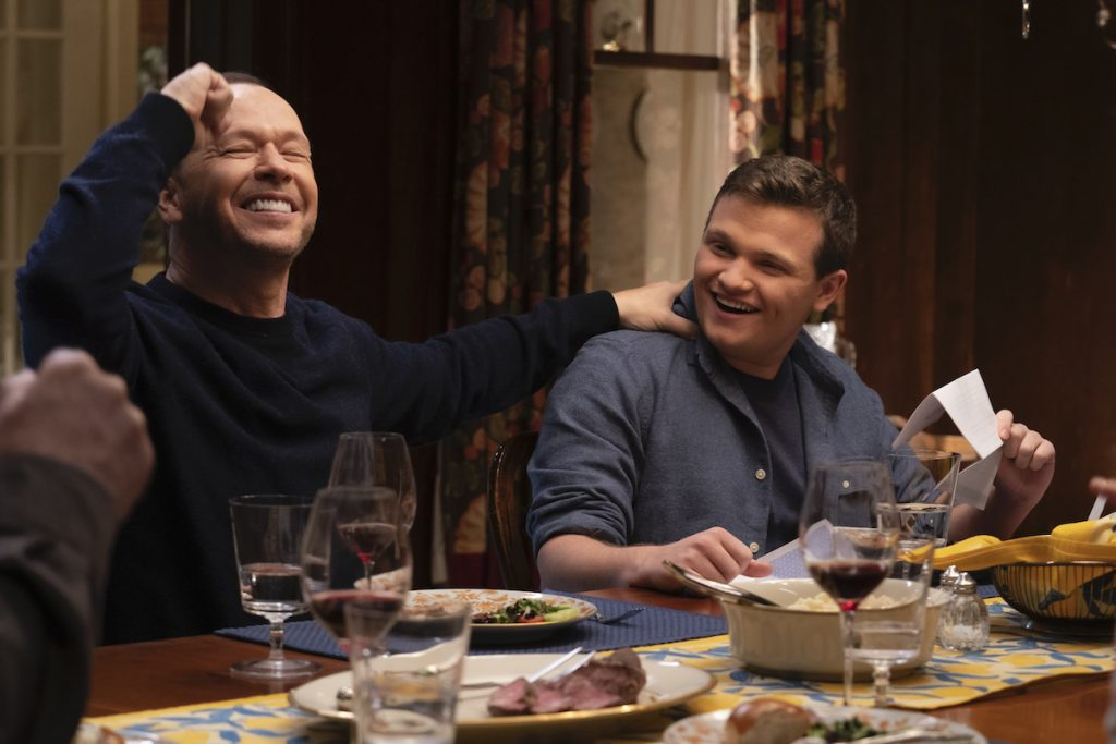 Donnie Wahlberg as Danny Reagan and Andrew Terraciano as Sean Reagan sit next to each other at the dinner table celebrating on 'Blue Bloods'