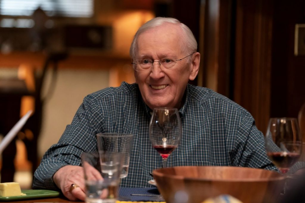 Len Cariou as Henry Cariou sits at the dinner table smiling in 'Blue Bloods