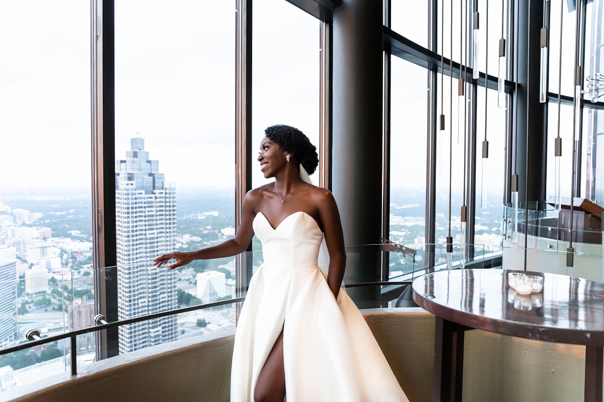 Briana Morris from 'Married at First Sight' gazing out the window of a hotel at the Atlanta skyline in her wedding gown on her wedding day