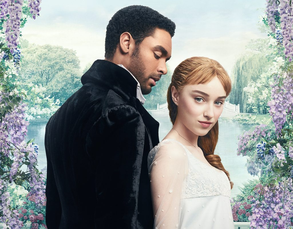 Regé Jean-Page and Phoebe Dynevor stand in front of a frame fo flowers in 'Bridgerton' | Netflix