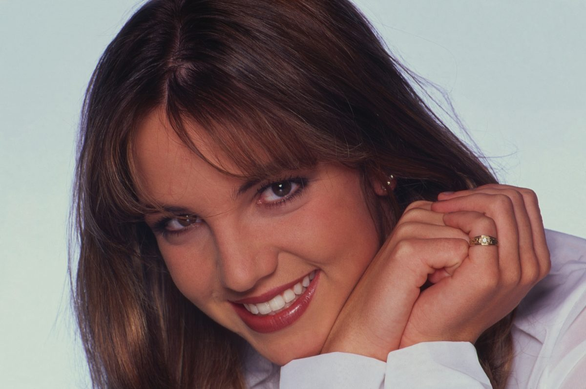Portrait of American pop singer Britney Spears during a promotional photo shoot at Munich, Germany 2000. The photo is a close-up of the singer with her hands together under her chin. She's smiling and looking at the camera.